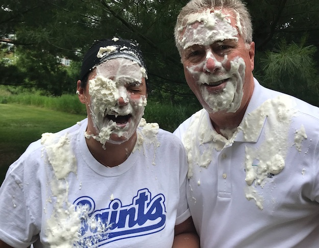 two people hit in the face with pie